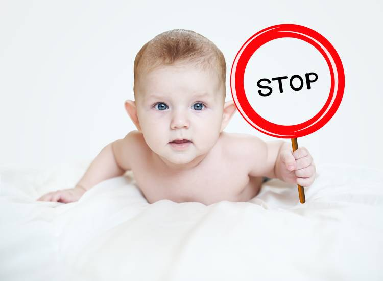 baby holding a STOP sign